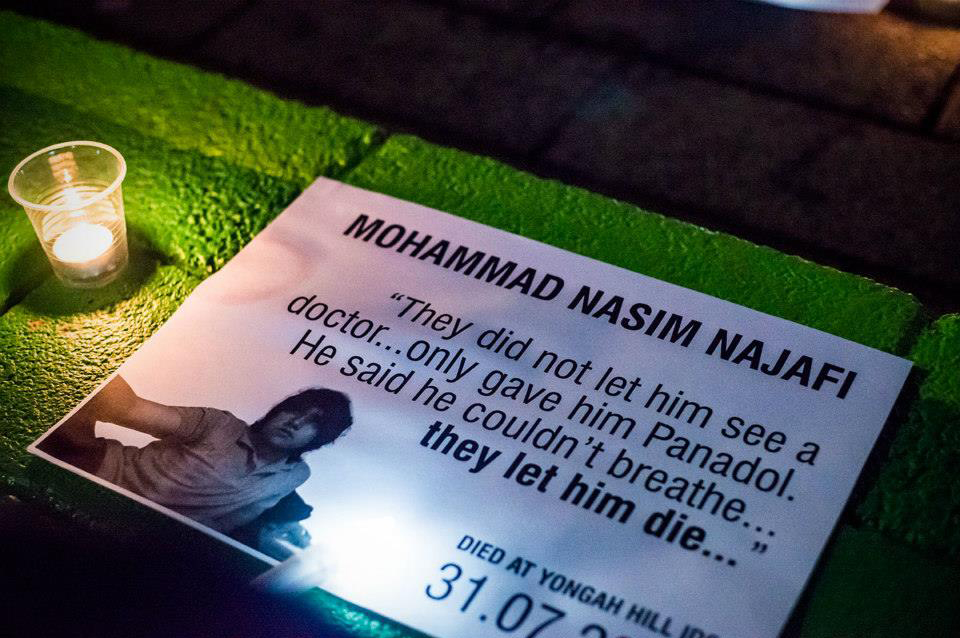 Candle and placard at vigil for Mohammad Nasim Najafi.
