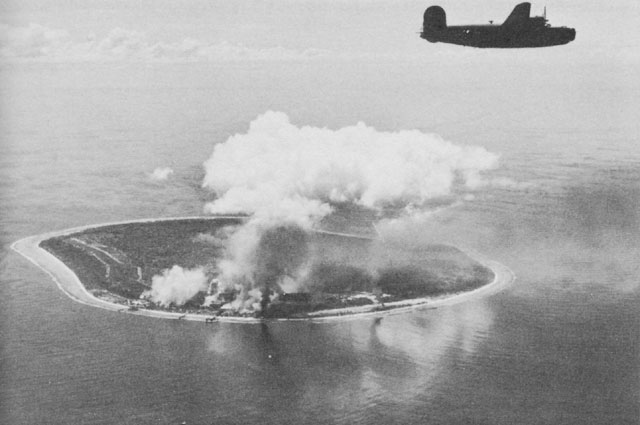 A view of the island of Nauru being bombed. Clouds of smoke rise from the island as a plane flies overhead.