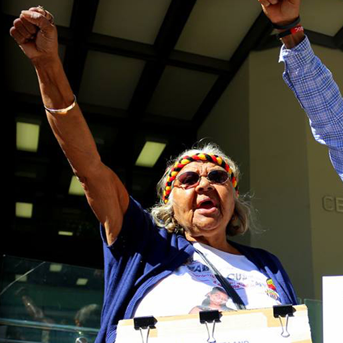 Aunty Carol raises her right fist in the air while holding a placard in the other hand outside the Coroner's Court in an act of resistance.