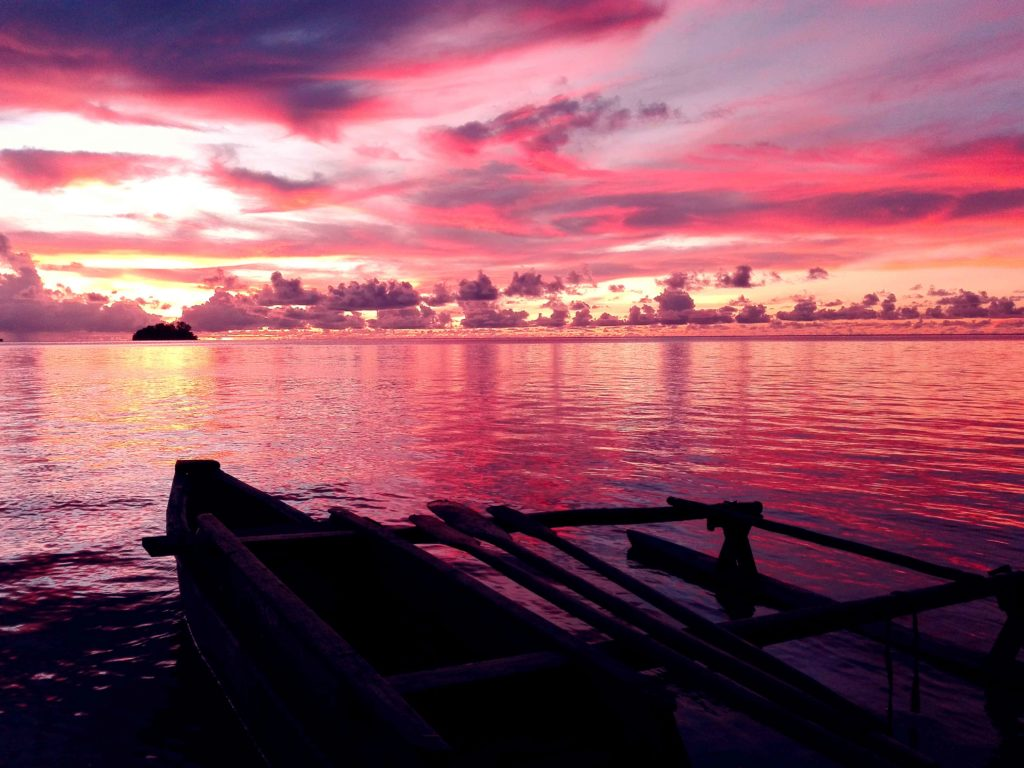 A photograph by Kaaveh Maleknia, a man detained on PNG shows a the ocean and sky at sunset. It is taken from the shore just in front of a small boat that is silhouetted against the backdrop of a luminous, bright pink and purple, cloudy sky that is reflected in the ocean. The silhouette of a small island can be seen in the background.