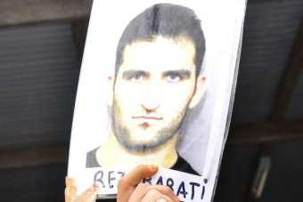 A laminated photo of Reza Barati with his name written beneath his image, is held up in the Manus Island Detention Centre.