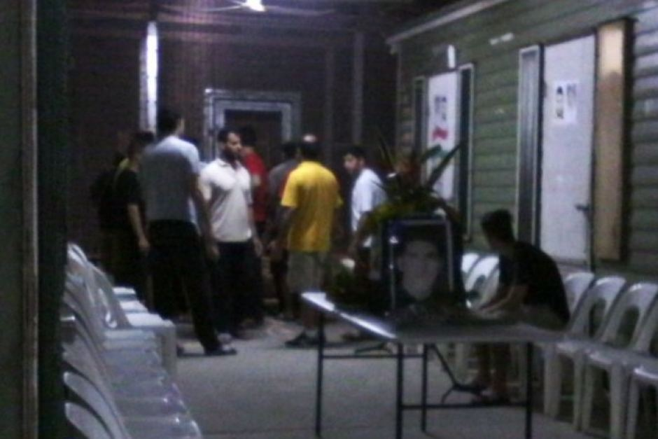 It's night time at the Manus Island Detention Centre. A small group of men gather in an area that appears to be between two buildings. Plastic chair line both sides. A plastic fold out table sits in the centre of the frame. There are plants on the table and a frame photo fo Reza Barati. One man sits on a chair, while the rest stand, gather at the end furthest from the camera. Reza Barati's photo has also been stuck on one of the doors.