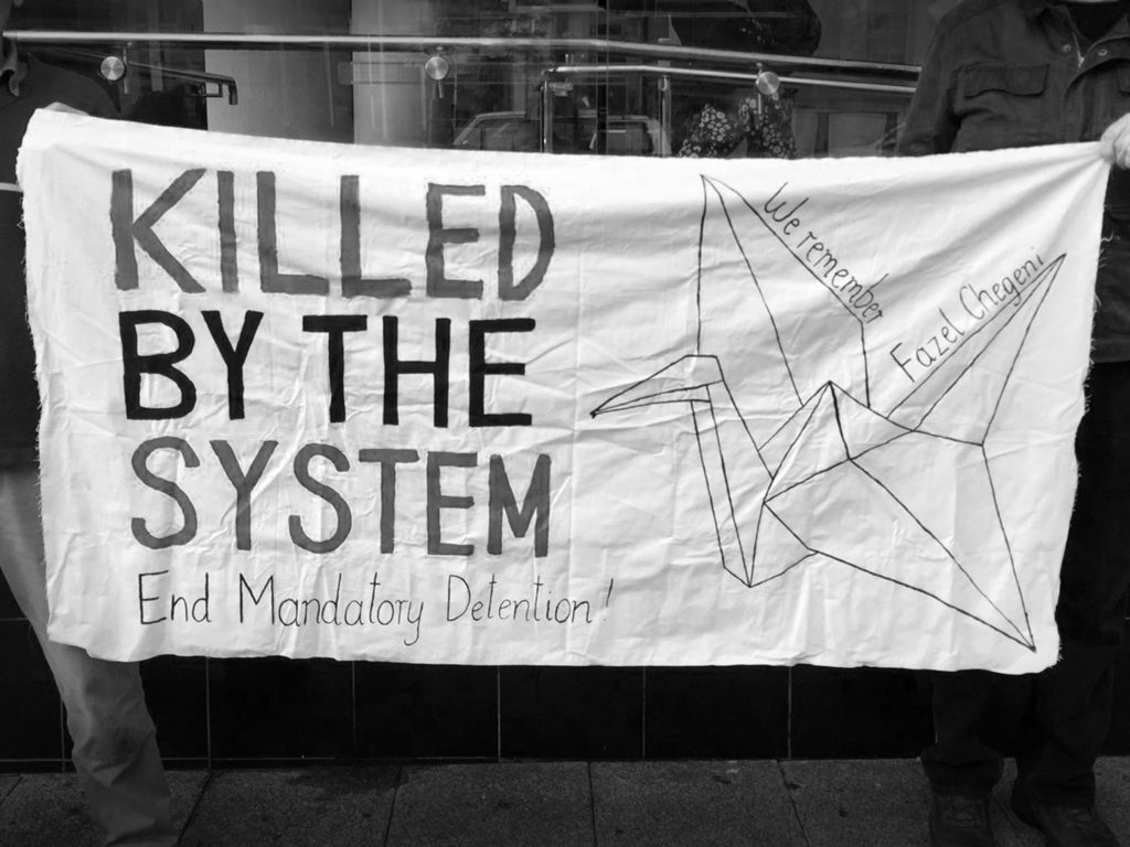 A close up photo of a banner held outside the Perth Coroner's Court. It reads 'Killed by the System. End Mandatory Detention!' on the left side and on the right is a drawing of a paper crane with the words 'We remember Fazel Chegeni'.