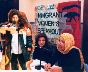 A photo of a woman standing and speaking at a public event is collaged on top of a photo of two women sitting behind tables, speaking on a panel. In the background a banner is draped over a board. It reads 'Immigrant Women's Speakout'.