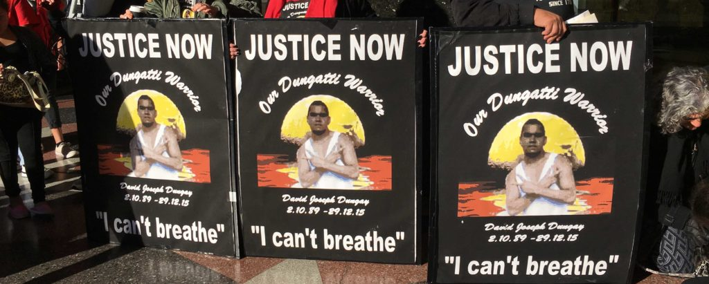 Three 'Justice Now' placards for David Dungay held in a row outside the court.