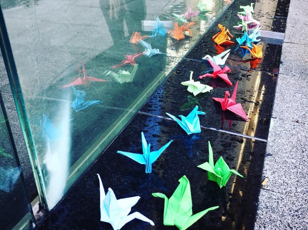 Small coloured paper cranes line a low wall. The cranes are reflected in a glass pane behind the wall. The ledge is wet from rain earlier in the morning.