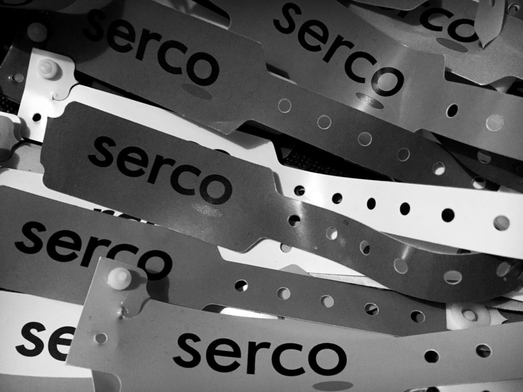 Plastic wrist bands with the word 'Serco' printed on them, similar to tags provided in hospital.