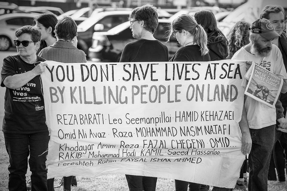 Activists hold banner naming those who've died as a result of Australia's border policies. Main text reads 'You don't save lives at sea by killing people on land'.