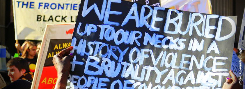 A photo taken by Charandev Singh at a Black lives matter protest in Melbourne. A close up of a placard reads 'We are buried up to our necks in a history of violence + brutality against people of colour'.