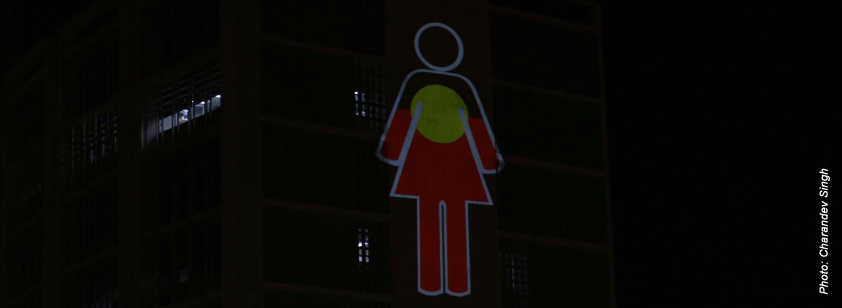 A photo taken by Charandev Singh of a projection onto the old police lockup in Perth. It is of an icon of a woman overlayed with the Aboriginal flag.