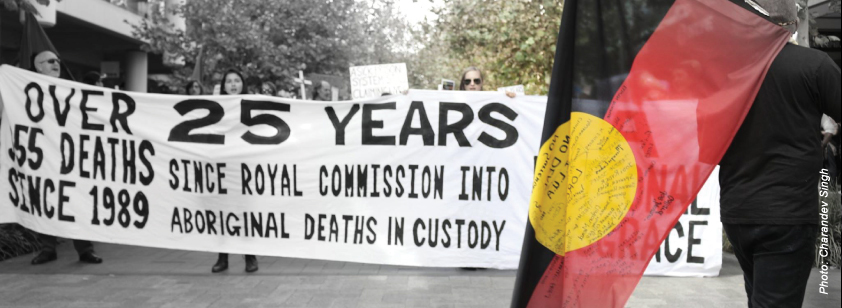 A photo taken by Charandev Singh shows a man holding an Aboriginal flag in the foreground. In the background a group of protestors at a rally hold a banner highlighting the number of deaths in custody since 1989. It also reads '25 years since Royal Commission into Aboriginal deaths in custody / A national disgrace'.