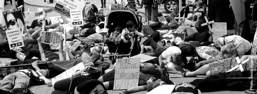 A photo taken by Jacob Higgins show people participating in a die-in outside the coroner's court. In the centre of the crowd are two children sitting in a pram.