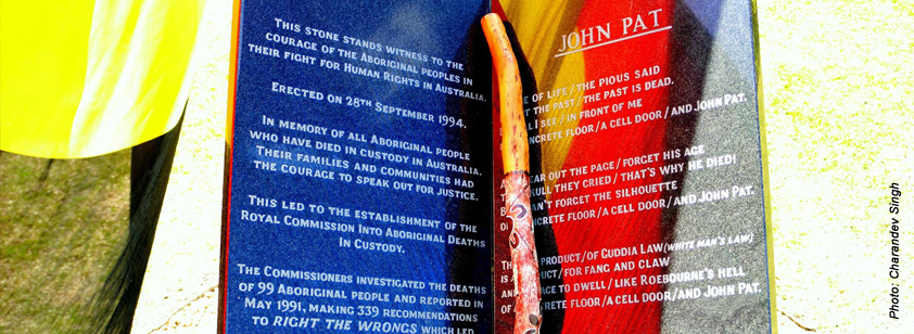 A photo taken by Charandev Singh of a close up of the John Pat Memorial at the old Fremantle Prison. A didgeridoo lies across it and the Aboriginal flag is reflected in the marble memorial.