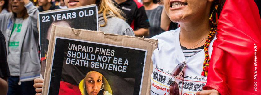 Photo taken by Marziya Mohammedali at a protest for Ms Dhu. A woman is seen carrying a placard of Ms Dhu that says 'Unpaid fines should not be a death sentence', in the other hand she carries an Aboriginal flag. She wears a stop deaths in custody shirt organised by Ms Dhu's family.