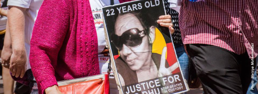 A photo taken by Marziya Mohammedali, shows a placard carried at a march that reads '22 years old. Justice for Ms Dhu. Stop Deaths in Custody'. It should a photo of Ms Dhu holding up the peace sign.