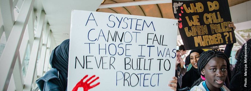 A photo taken by Marziya Mohammedali at a Black Lives Matter rally in Perth. A young woman holds up a sign that reads 'A system cannot fail those it was never built to protect' with a red handprint on one side. Another woman carries a placard that reads 'Who do we call when police murder?!'