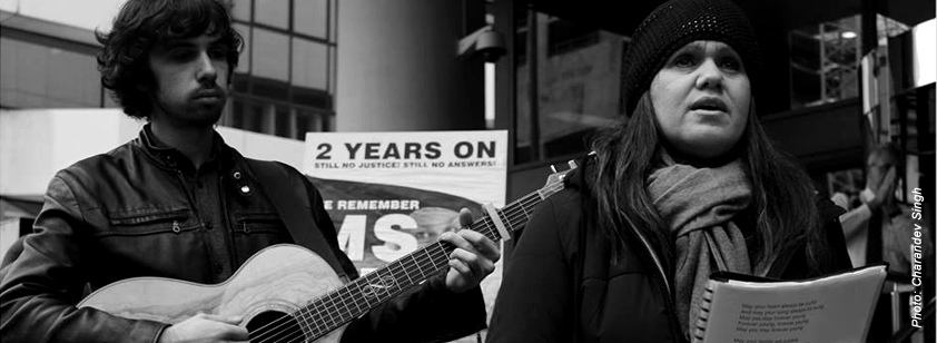A photo taken by Charandev Singh shows a son and mother performing a song outside the Perth Coroner's court. The son plays the guitar while the mother sings 'Forever Young'. In the background a placard can be seen that reads '2 years on: still no justice, still no answers. We remember Ms Dhu'.