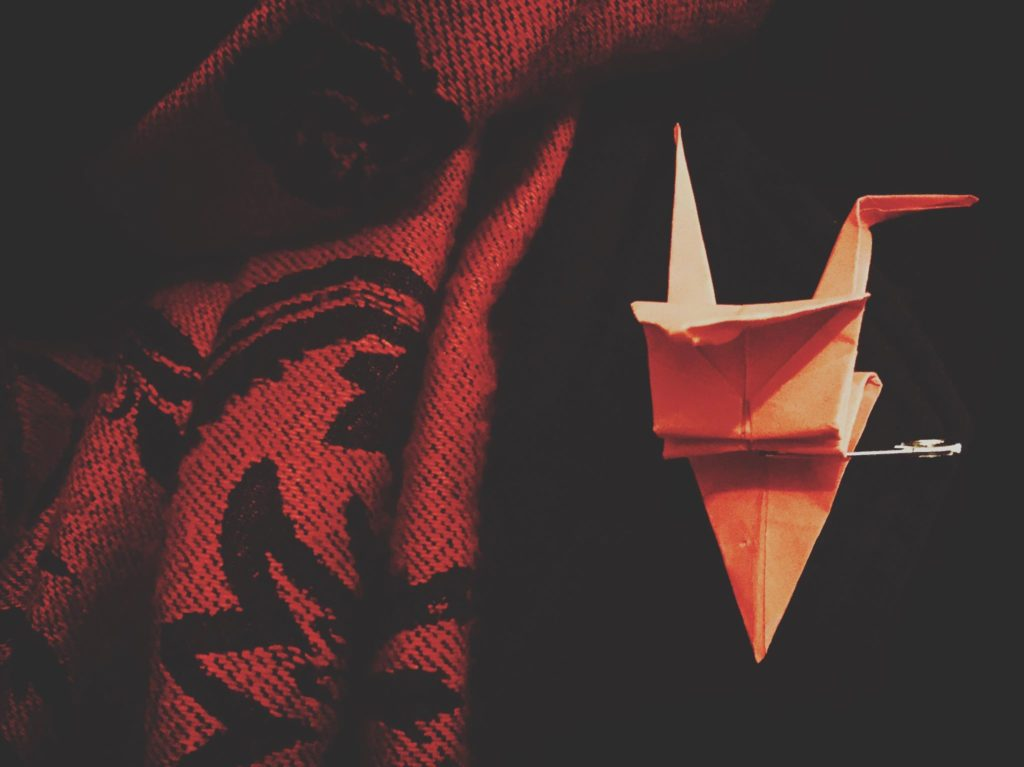 A paper crane pinned on jacket.