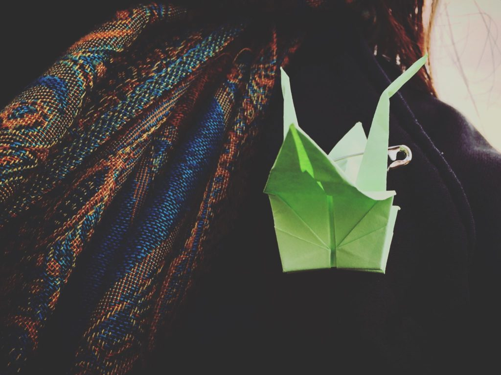 A paper crane pinned to a jacket.