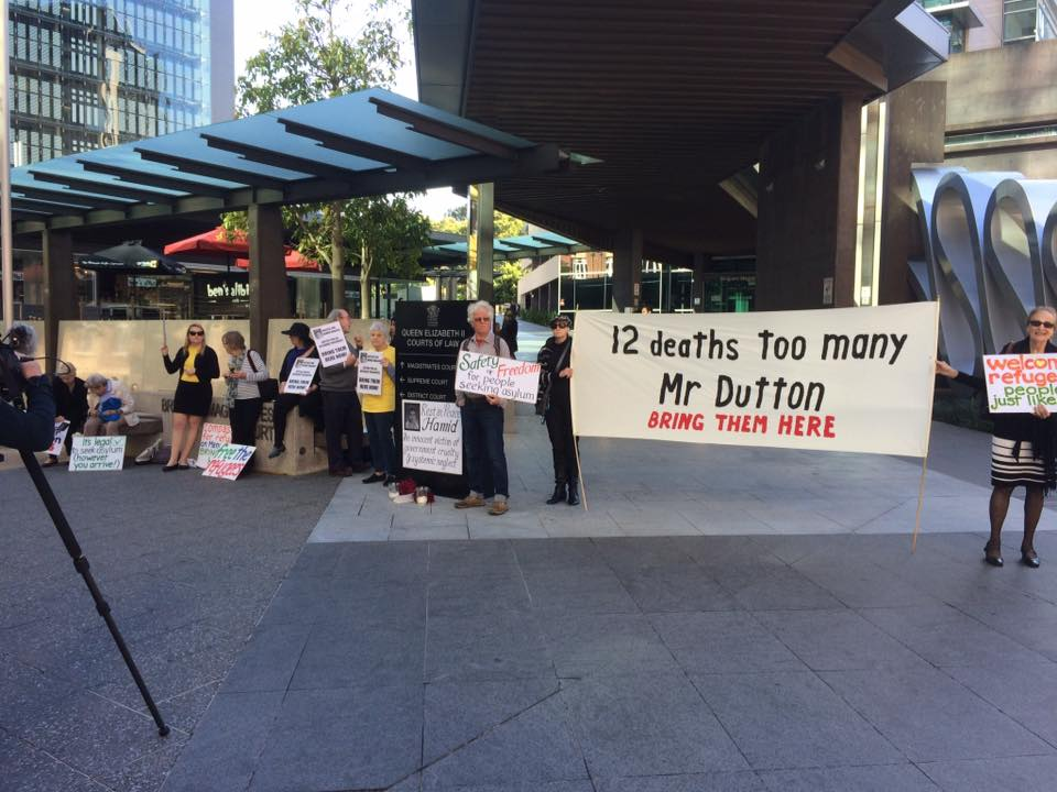 Refugee rights supporters gather outside the Coroner's Court in Brisbane. They hold placards and a banner that reads '12 deaths too many Mr Dutton. BRING THEM HERE'