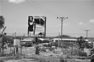 A billboard is shown that reads 'Migrating? Make a Plan'. A fence is in the foreground and buses can be seek parked in the background.