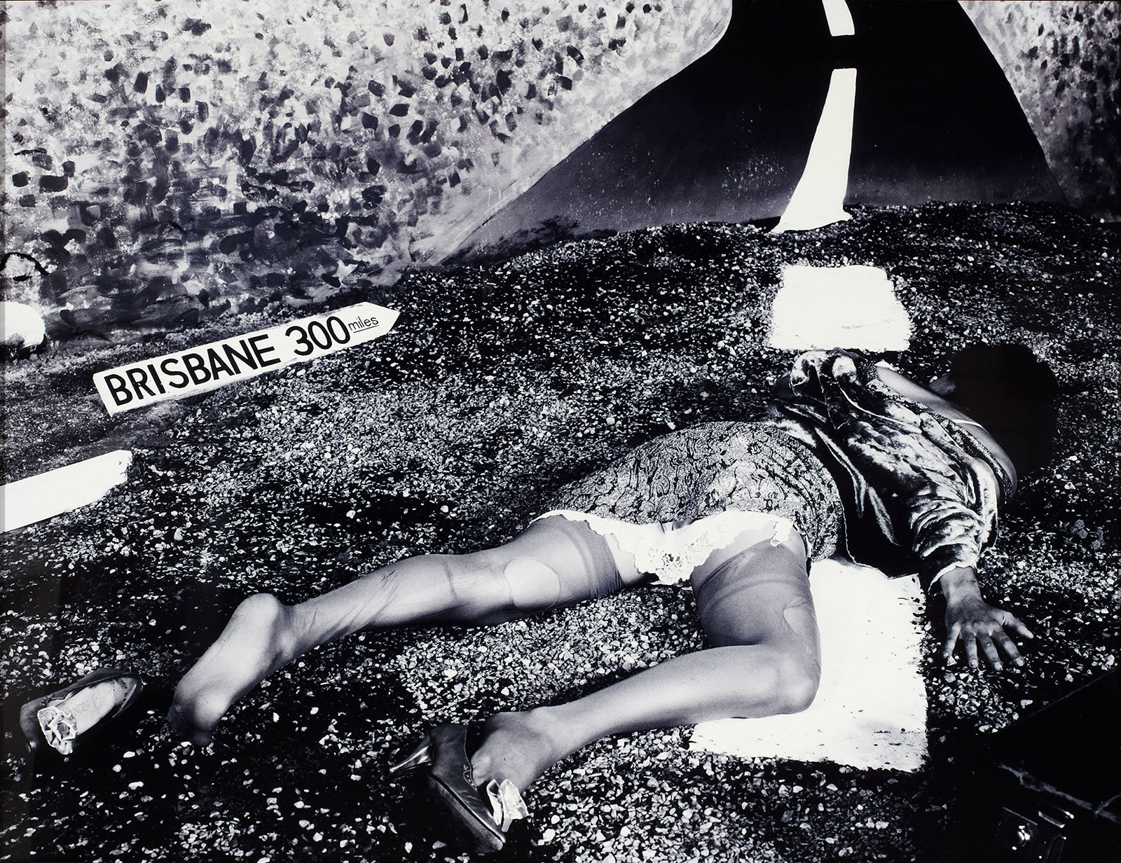 A woman lays face down, sprawled across the centre of a road. Her stockings are torn and her shoes are falling off. A broken street sign lays on the road beside her indicating Brisbane is 300km away. There is no one else in sight.