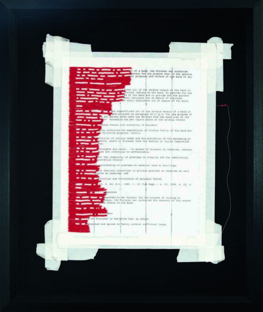 Sitting within a black frame and background is a page of the Canadian Indian Act. Red beading overlays a section of the document on the left side. On this section, white beads replace the words below, rendering the Act null and void.