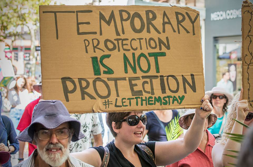Placard held at protest reads 'Temporary Protection is Not Protection #LetThemStay'