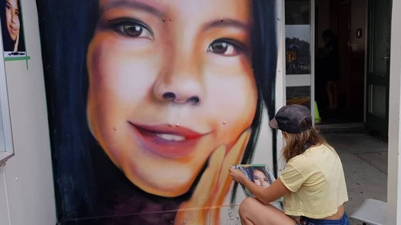 A mural of Tina Fontaine, a teenager girl with dark eyes and hair and a broad smile, being painted onto a wall by another teenage girl.