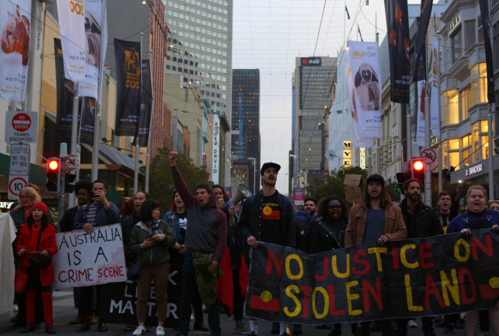 A protesting crowd stands in the middle of an intersection. They carry a banner that reads 'No Justice on Stolen land' and a placard that says 'Australia is a crime scene'. There are Aboriginal flags painted on the banner and on the shirt of one of the men carrying it.