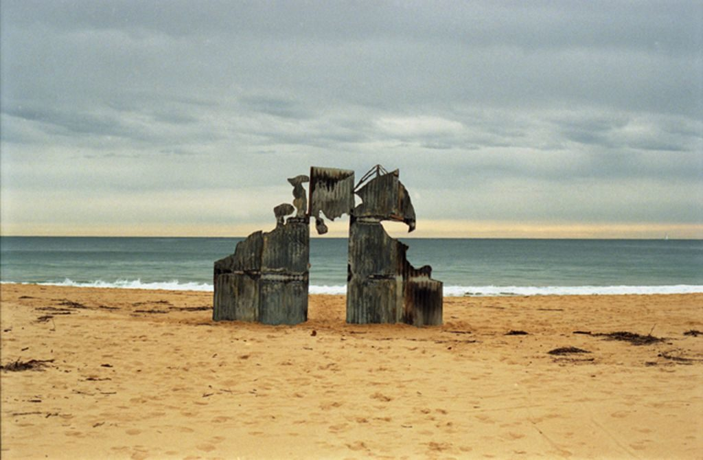 A large corrugated iron cutout of Géricault's 'The Raft of Medusa' sits on the shore of a beach in NSW. The viewer is positioned to look through and around this cutout towards the coastline and horizon in the background.