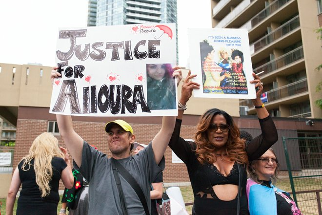 At a Trans March two people hold up placards. One reads 'Justice for Alloura' with a photo of Alloura at the bottom right and love hearts drawn around her name.