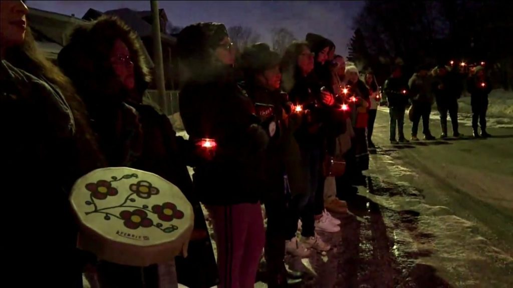 A group of women gather along a street, on a cold, snowy night. It is so cold you can see their breaths. At this vigil, they carry candles and traditional drums.