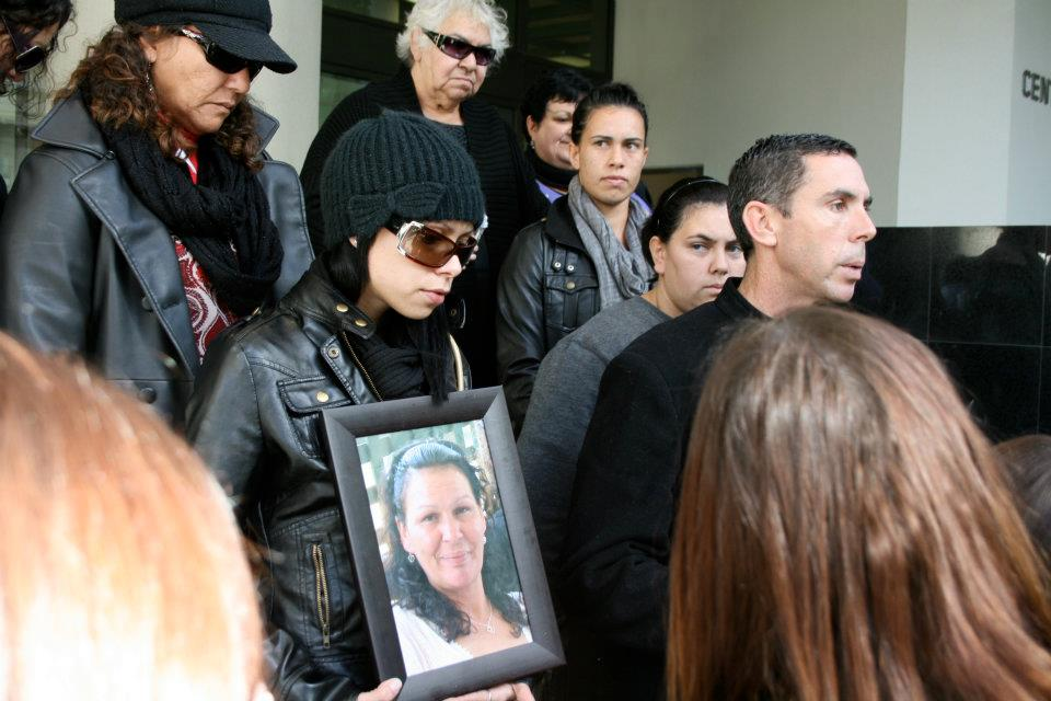 Half a dozen family members, including Andrea's Mother and siblings, can be seen gathered on the steps in front of a court building. The woman at the front in the foreground holds a framed photo of Andrea Pickett. Everyone in the photo is wearing black clothes and about half wear black sunglasses to cover their eyes.