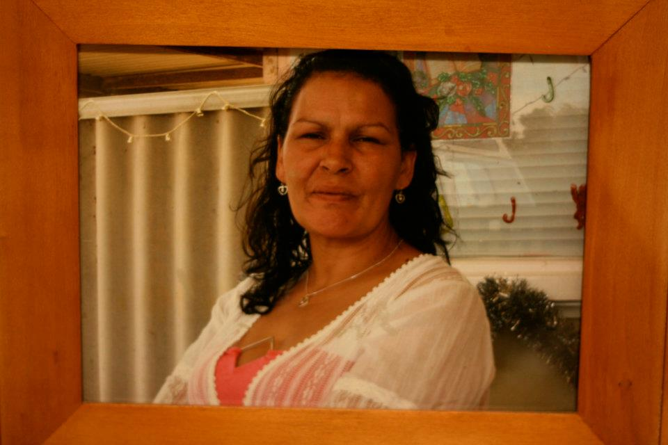 A framed photo of Andrea Pickett. In this photo she looks towards the camera. She's wearing a white blouse over a coral coloured singlet, with earrings and a necklace. She appears to be standing under a patio with a fence visible in the background that is decorated with Christmas lights and tinsel.