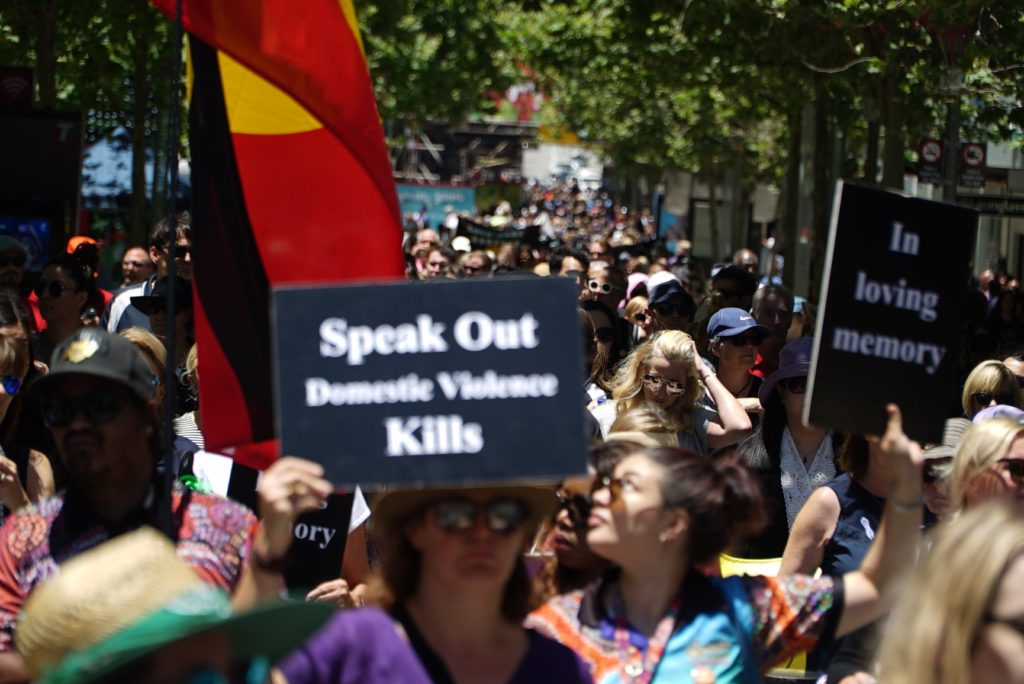 A large crown of people are march down the street. Two people hold placards at the front of the march, one says 'Speak Out Domestic Violence Kills' and the other reads 'In loving memory'. To the left and just behind these placards is an Aboriginal flag being carried down the street.