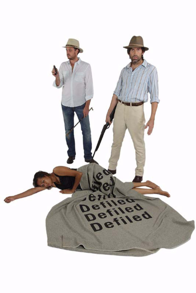 An Aboriginal woman lays on the ground facing the camera with her body strewn across the floor. A blanket printed with the words 'Defiled' is draped over her waist, hips and legs. Two white settler men stand above her as if they have been caught while hunting their prey. One holds a rifle which is pointed down towards her and stares into the camera. The other appears preoccupied with something he's holding in his hand.