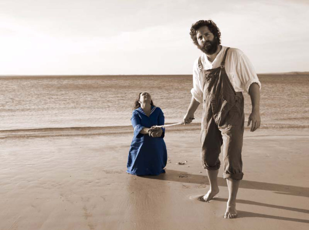An Indigenous woman wearing a long blue dress is kneeling on wet sand at a beach with the ocean behind her. Her hands are bound together with rope that is being pulled by a white man who is trying to drag her across the sand. Her head is up looking toward the sky as if she is trying to resist his strength and crying out. He looks casually at the camera.