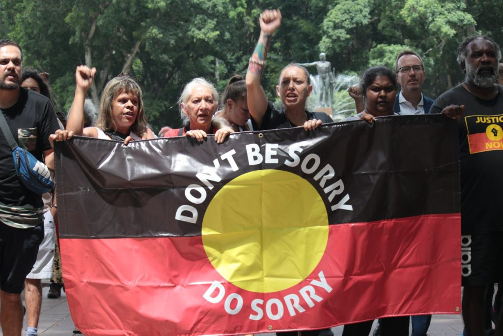 A group of staunch Aboriginal women carry a banner with the words 'Don't be sorry do sorry' printed across an Aboriginal flag. Two of the women have their fists raised in the air. They are marching in a protest and other people can be seen walking with them.