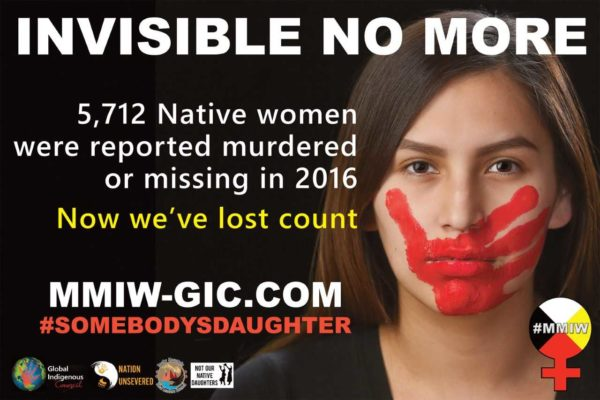 An Indigenous woman looks directly at the camera. On her face is a red handprint that covers her mouth. The accompanying text reads 'Invisible no more. 5,712 Native women were reported murdered or missing in 2016. Now we're lost count. MMIW-GIC.COM #Somebodysdaughter'