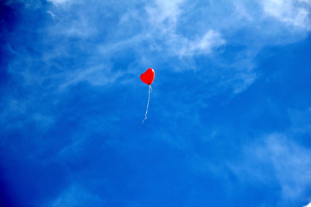 A single red, heart shaped balloon floats up into the bright blue sky.