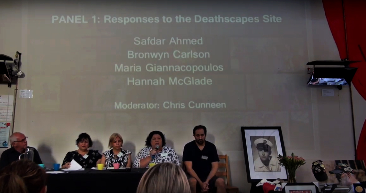 Five people sit on a stage behind a table. Projected text behind them reads 'Panel 1: Responses to the Deathscapes Site: Safdar Ahmed, Bronwyn Carolson, Maria Giannacopoulos, Hannah McGlade. Moderator: Chris Cunneen'. To their right is a large framed photo of Uncle Ray Jackson, a bouquet of flowers and other memorabilia.