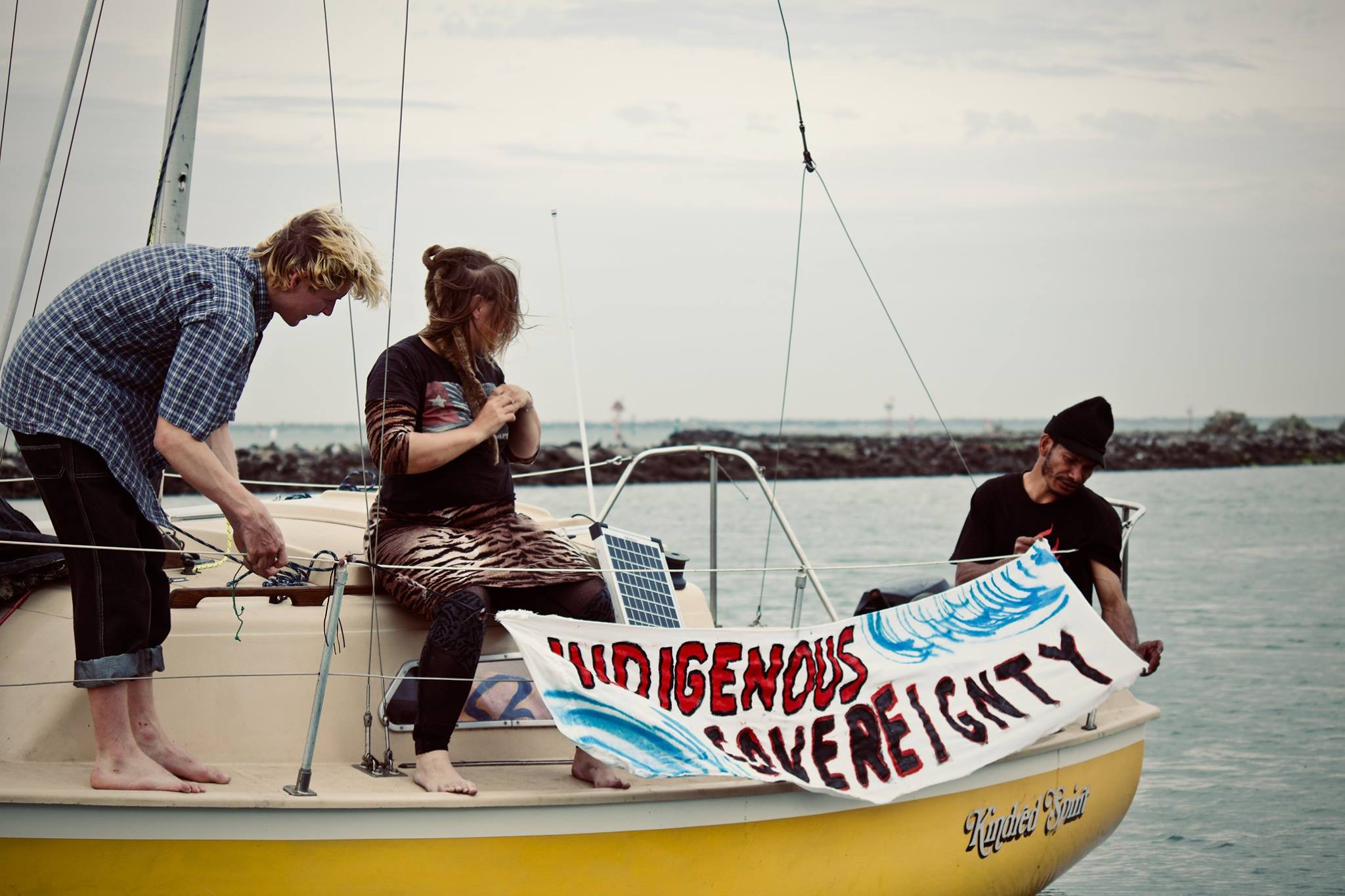 Two people sit on a yellow fibreglass boat. Another person stands bent over while fastening a banner to the boat railing. The banner reads 'Indigenous Sovereignty'.