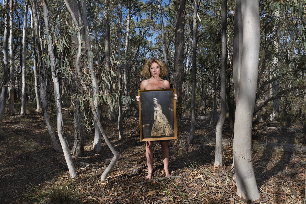 Amala Groom stands in bushland surrounded by thin, tall trees. Her stance is strong and defiant. She holds a framed painting of Queen Elizabeth II in front of herself, obscuring her naked body with this symbol of the crown and colonial project.