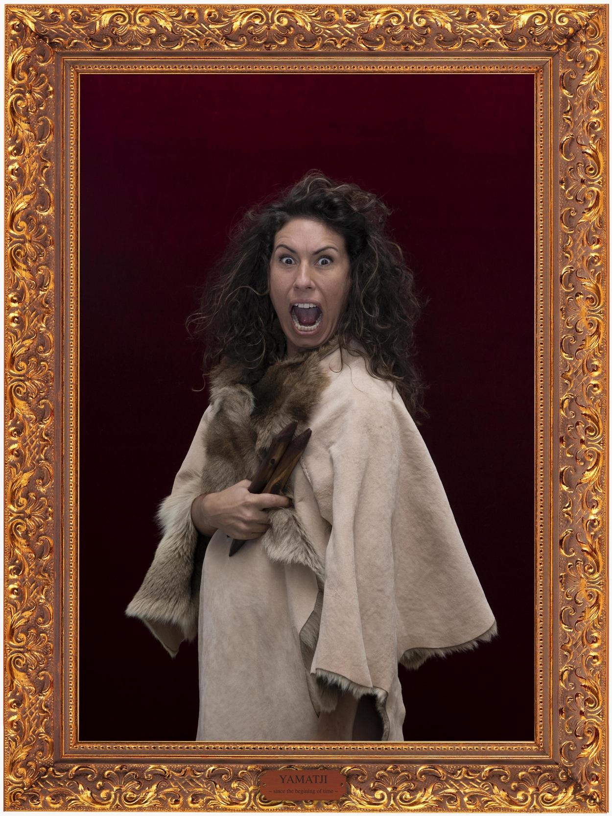 The image is a portrait of one of the artists, Nicole Monks who wears a skin/fur coat and holds in one hand two clapping sticks. She stares into the camera with eyes wide and mouth open as if she is screaming. The photo is in a gold frame with a plaque at the bottom which reads 'Yamatji - since the beginning of time'.