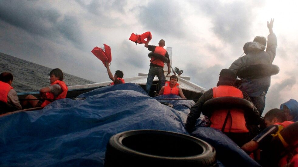 A group of men on a boat signal for help off the coast of Sumatra. They wave their arms and some hold orange life jackets up in an effort to attract attention. The photo is taken from the perspective of a person sitting in the middle of the boat looking towards the front. The horizon is on an angle, suggesting that the boat unstable, swaying from side to side. There is a black floatation ring in the foreground and a few of the men wear them around their waists in addition to the life jackets.