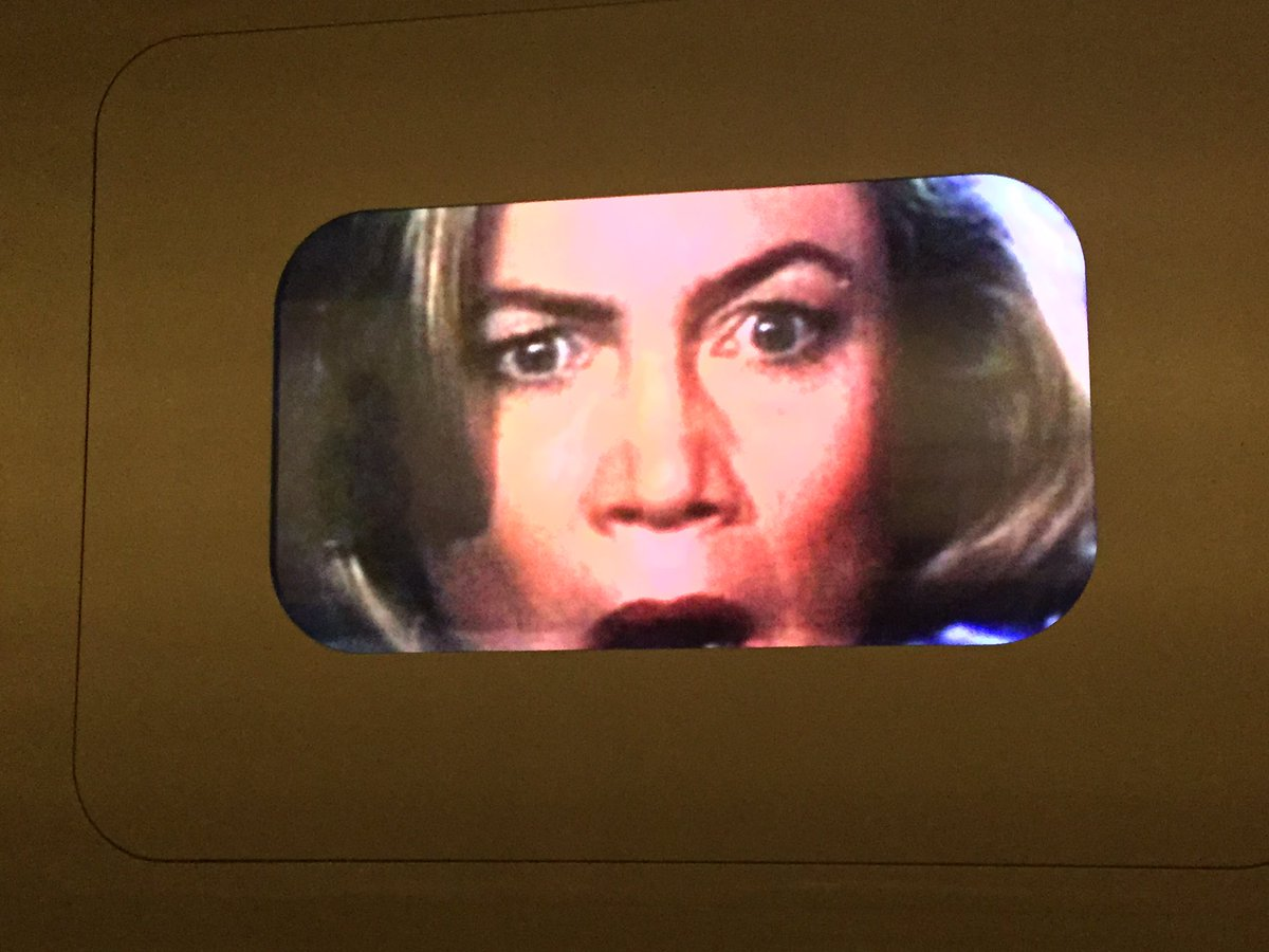Emerging from a frame akin to an old TV screen is the face of a white actress with wide eyes and her mouth open in shock.