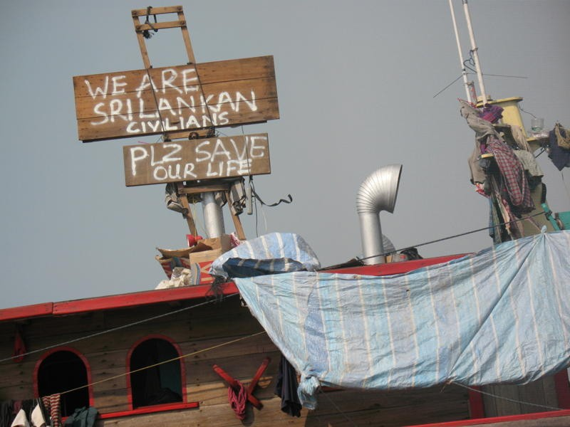 A spray painted timber sign erected on an asylum seeker boat reads 'We Are Sri Lankan Civilians. Plz Save Our Life'.