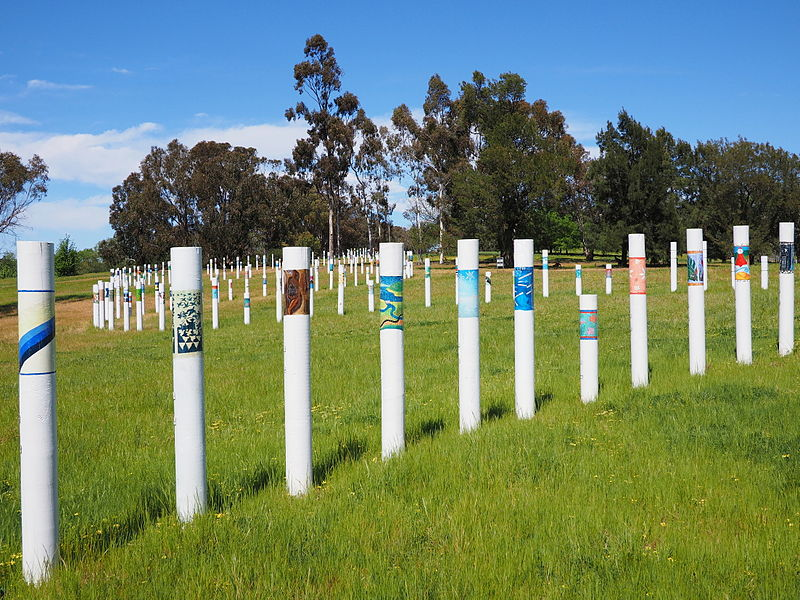 The SIEV X memorial. Pictured are a series of white poles of varying heights emerging from a grassy park. The poles have small drawings wrapped around them.