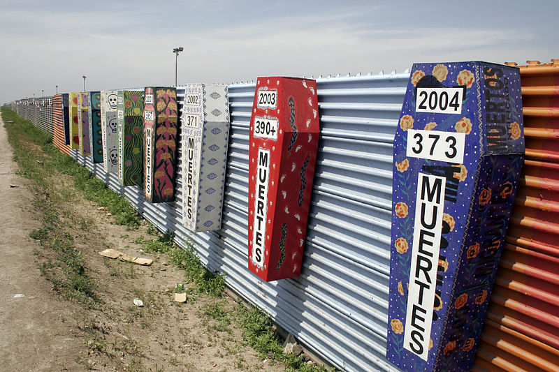 Colourful decorated coffins mounted on a corrugated steel fence at the border. Each coffin marks a year and the number of deaths during that year.